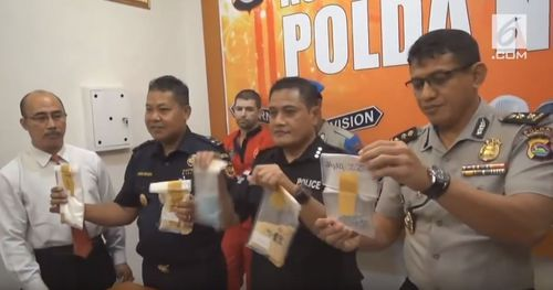 Felix Dorfin (third from left, in orange) was arrested in September for allegedly carrying a false-bottomed suitcase filled with four kilograms of drugs at the airport on Lombok.