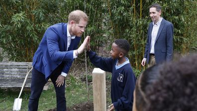 Duke of Sussex high fives with Asher Charles-Bowen after planting a tree from the Woodland Trust at St Vincent's Catholic Primary School.