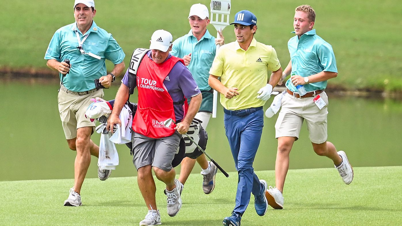 Joaquin Niemann of Chile runs with his caddie Gary Matthews on the 18th hole, breaking the record