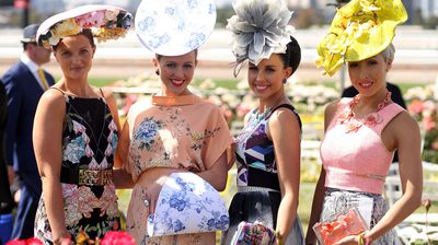 Racegoers pose on Oaks Day at Flemington Racecourse. (Getty)