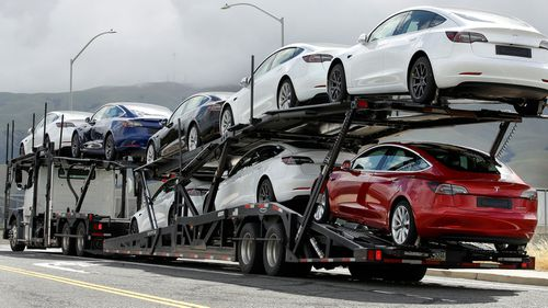 A truck loaded with Tesla cars departs the Tesla plant in Fremont, California.