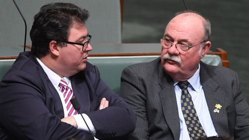 Coalition backbencher George Christensen speaks to Liberal party backbencher Warren Entsch during Question Time (Image: AAP)
