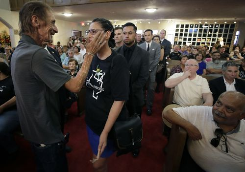 Antonio Basco wipes a tear from the eye of Patricia Vargas at the funeral of his companion of 22 years, Margie Reckard, at La Paz Faith Memorial & Spiritual Center.
