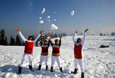 Indian tourists play with snow at Kongdoori tourist resort in Gulmarg north of Kashmir, some 60km from Srinagar, the summer capital of India's Kashmir.