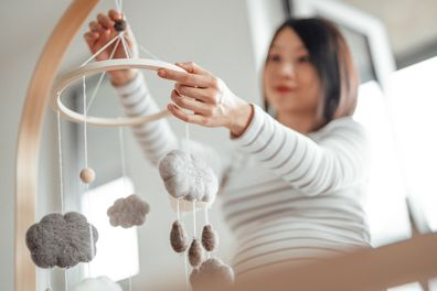 Pregnant woman hanging mobile over cot in nursery