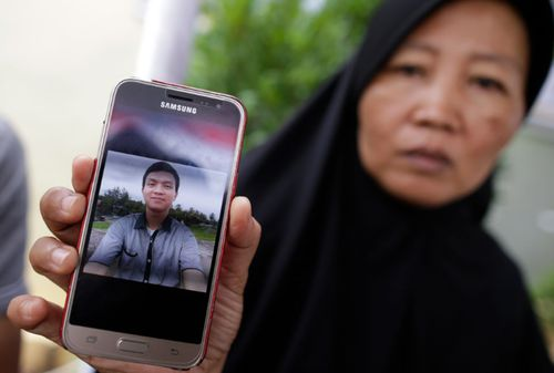 Yeni, 47, shows a picture of her son Muhammad Rafi, one of the plane crash victims, as relatives wait for the news of the forensics inspection in Jakarta.