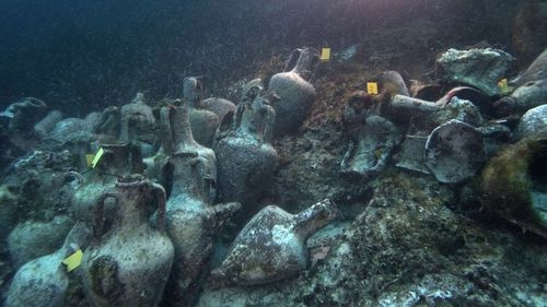 Ancient amphoras lie at the bottom of the sea from the shipwreck.