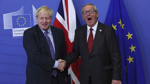 FILE - In this Thursday, Oct. 17, 2019 file photo British Prime Minister Boris Johnson shakes hands with European Commission President Jean-Claude Juncker during a press point at EU headquarters in Brussels.