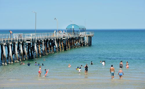 Beachgoers cool down in the water beside Henley Jetty in Adelaide. (AAP)