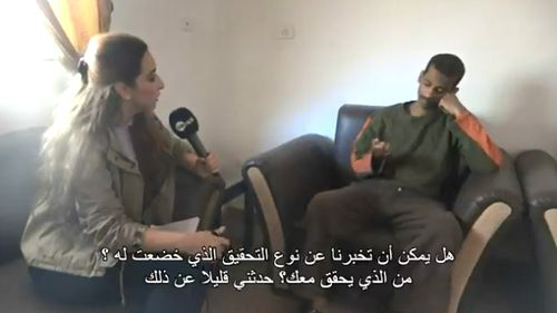 """Reporter Jenan Moussa sits next to an unshackled El Shafee Elsheikh, during an interview with the now captured member of ISIS beheading cell, """"The Beatles"""". (Twitter: Jenan Moussa)"""
