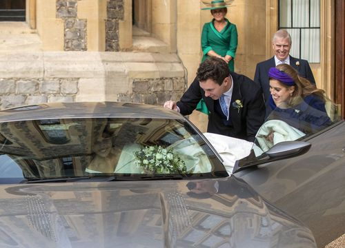 Princess Eugenie squeezes into the car, train and all, with a bit of help from new hubby and sis.