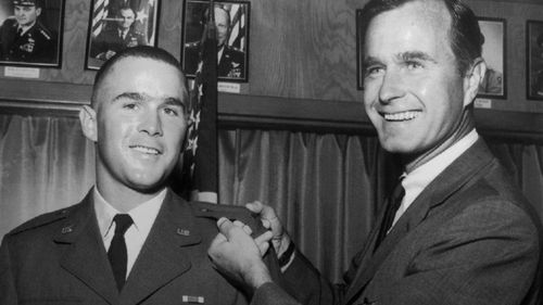 George H.W. Bush, right, is about to pin a lieutenant bar on his son, George W. Bush, after the younger Bush was made an officer in the Texas Air National Guard in Ellington Field, Texas in 1968.