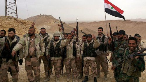 Syrian government soldiers holding the national flag and posing during an operation in Palmyra. (Supplied/ Syrian Arab News Agency)