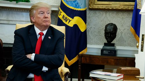 President Donald Trump listens during a meeting with North Korean defectors where he talked with reporters about allowing the release of a secret memo. (AAP)