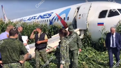 Video footage released by the Russian Investigative Committee shows investigators near the Ural Airlines A-321 passenger plane on the site of its emergency landing in a field.