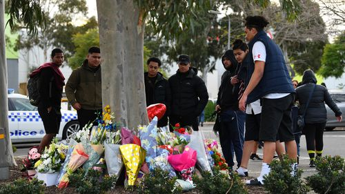 Mourners are seen at the location where a fifteen year old was fatally stabbed outside Brimbank Shopping Centre, Melbourne, Wednesday, June 17, 2020.