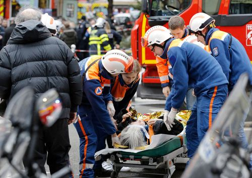 Emergency workers treat an injured woman after the explosion in Paris.