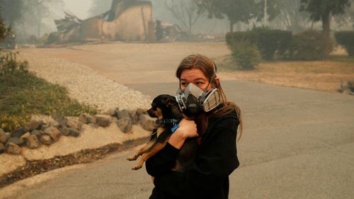 Araya Cipollini, 19, holds on to her dog T.J. near the burned out remnants of her neighbor's home.