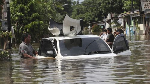 A resident inspects a car flooded neighbourhood in Tanggerang outside Jakarta, Indonesia, Thursday, Jan. 2, 2020.