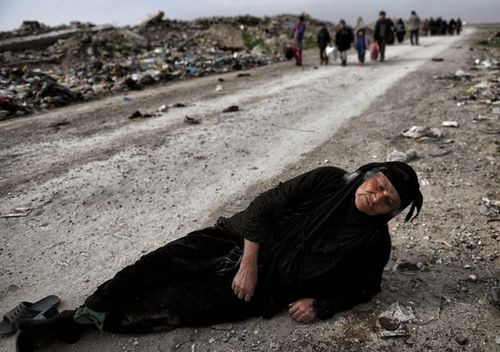 An Iraqi woman lies on the ground as civilians flee Mosul while Iraqi forces advance inside the city during fighting against Islamic State group's fighters on March 8, 2017 (AFP)