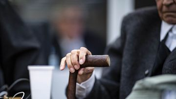 A former 94-year-old SS guard holds his walking stick at the beginning of a trial in Muenster, Germany, Tuesday, Nov.6, 2018. He is charged of accessory to murder for serving at the Nazis' Stutthof concentration camp. (Guido Kirchner/dpa via AP)