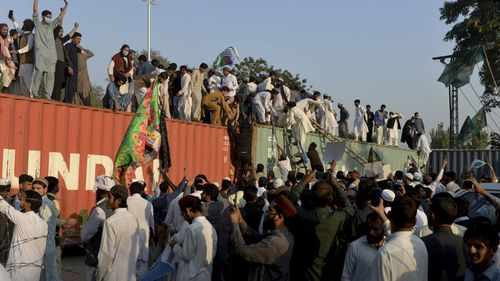 Protesters try to climb on a shipping container at a rally against French President Emmanuel Macron and republishing of caricatures of the Prophet Muhammad they deem blasphemous, in Islamabad, Pakistan, Friday, Oct. 30, 2020