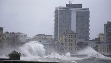 Waves surge over a sea wall in Havana. (AAP)