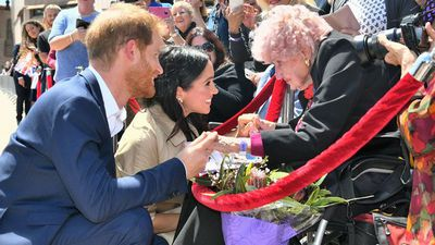 Prince Harry and Meghan Markle holding hands with Daphne Dunne, 98.