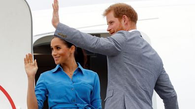 Meghan Markle and Prince Harry wave as they board plane during Australia and Pacific Islands Royal Tour in November 2018