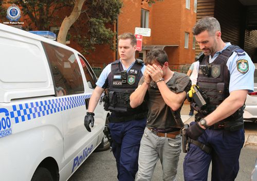 Police cuff and lead away a suspect during one of many raids carried out in the city before Christmas.