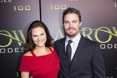 """Actors Cassandra Jean and Stephen Amell arrive on the green carpet for the Celebration of the 100th Episode of CW's """"Arrow"""" at the Fairmont Pacific Rim Hotel on Oct 22, 2016 in Vancouver, BC, Canada."""