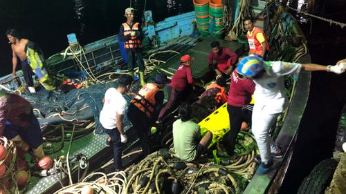Tourists from a boat that sank are helped onto a pier from a fishing boat. Picture: AAP