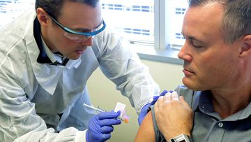 Pharmacist Michael Witte, left, gives Neal Browning a shot in the first-stage study of a potential coronavirus vaccine
