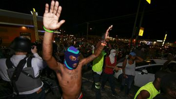 Demonstrators raise their hands during a rally on West Florissant Avenue to protest the shooting death of an unarmed teen by a police officer in Ferguson. (Getty Images)