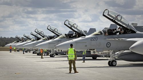 Ground crew assist as RAAF F/A-18F Super Hornets prepare for departure to the Middle East. (ADF)