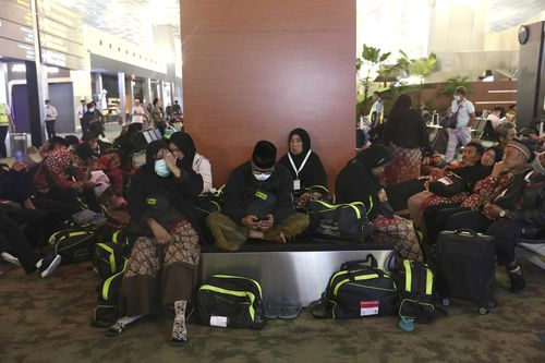 Indonesian who are scheduled to travel to Saudi Arabia for a minor pilgrimage, called 'Umrah', sit at a waiting area as they are turned away from their flights at Soekarno-Hatta International Airport.
