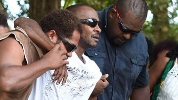 A man believed to be the father of some of the eight victims is held up by family members near the scene. (AAP)