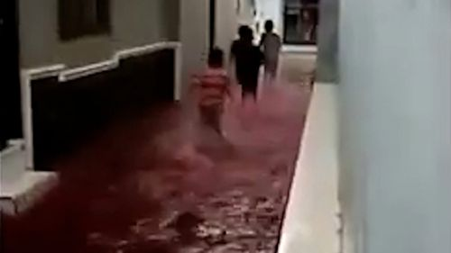 People walk through surreal blood-red waters.