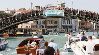 Fans cheer on the couple as they approach a bridge on Canal Grande.