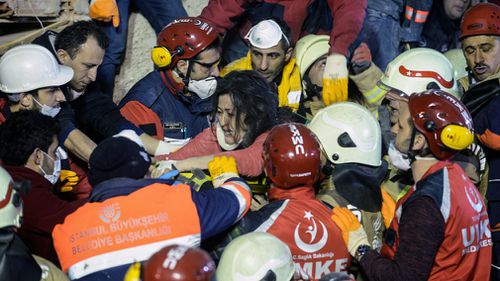 A woman reacts after being pulled from the rubble by rescue workers.