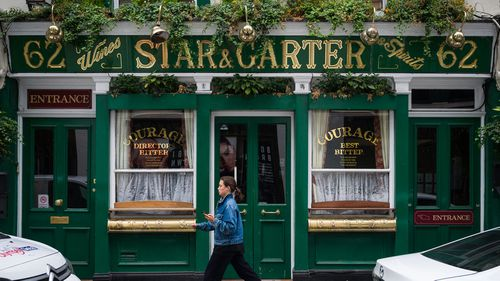 A woman walks past a temporarily closed pub on June 19, 2020 in London, England.