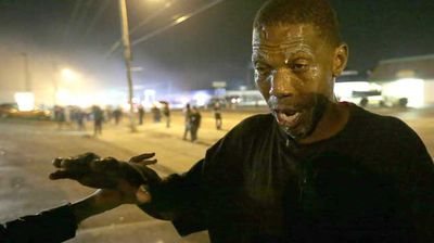 A protester tries to recover after being hit with tear gas. (AP)