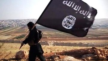 A man carries the Islamic State flag through a field, near an unknown town in the now fallen, self-declared caliphate.