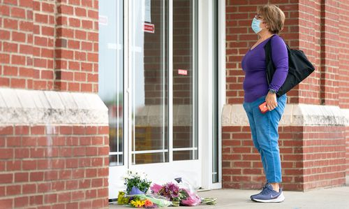 A woman reads a note explaining the temporary closure of Riverview Family Medicine and Urgent Care after the fatal shooting of Dr Robert Lesslie and four others on April 8.