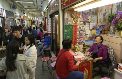 People line up at fortune-telling stalls outside Wong Tai Sin Temple.