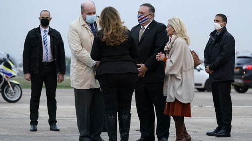 U.S. Secretary of State Mike Pompeo, third from right, and his wife Susan, third from left, speak with Jacques Jouslin de Noray of France's Ministry of Foreign Affairs, second from left, and U.S. Ambassador to France Jamie McCourt, second from right, after stepping off a plane at Paris Le Bourget Airport, Saturday, Nov. 14, 2020, in Le Bourget, France