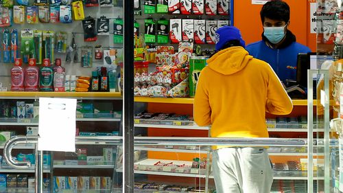 A shop attendant is seen wearing a face mask on August 02, 2020 in Melbourne, Australia. (Photo by Darrian Traynor/Getty Images)