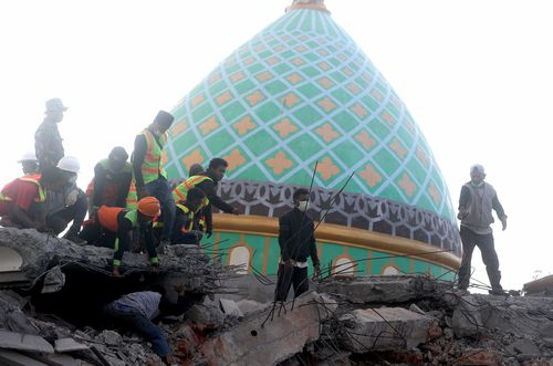 Indonesian rescuers uncovered two survivors from a pancaked mosque left behind from the Lombok earthquake that rattled the region over the weekend. Picture: AP.