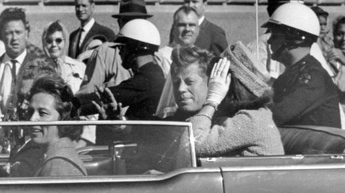 President John F. Kennedy waves from his car in a motorcade in Dallas on November 22, 1963. (AP)