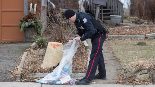 This Jan. 29, 2018, photo shows the discovery of dismembered skeletal remains in backyard planters and the police allegation that a serial killer is responsible for the gruesome crimes have prompted at least one homicide expert to suggest the perpetrator is likely a psychopath. A police officer is shown outside a house on Mallory Crescent in Toronto, where Bruce McArthur did landscape work. McArthur, 66, was charged Jan. 18 in the presumed deaths of five men. (Chris Young/The Canadian Press via AP)